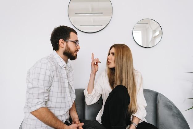 Frustriertes junges paar, das auf der couch sitzt und zu hause miteinander streitet.