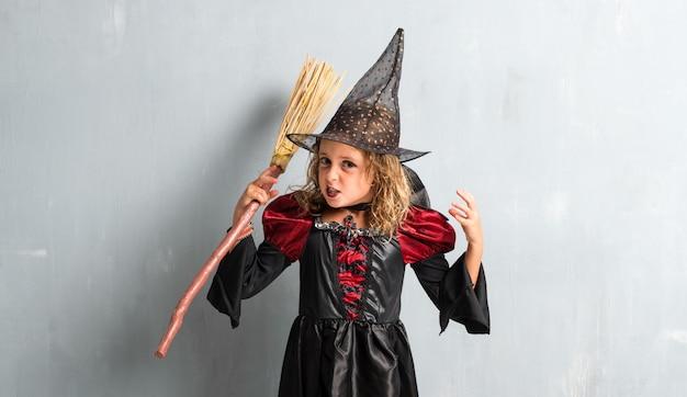 Frustriertes kleines mädchen kleidete als hexe für halloween-feiertage an