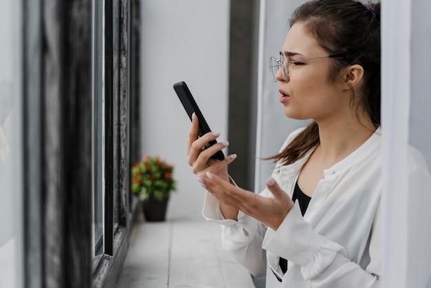 Frustriertes mädchen, das auf ihr telefon schaut