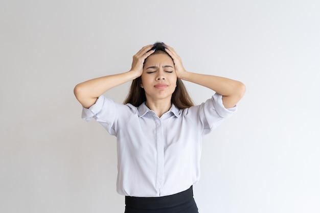 Frustriertes mädchen, das unter kopfschmerzen leidet