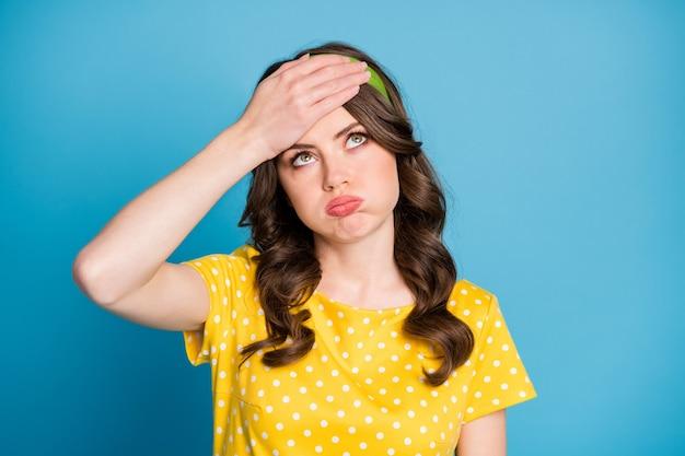 Frustriertes müdes mädchen berührt die stirn mit handblick kopienraum seufzer tragen gelbgrüne kleidung einzeln auf blauem hintergrund