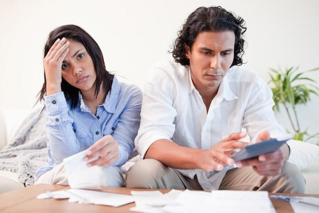 Frustriertes paar, das ihre berechnungen im wohnzimmer durchführt