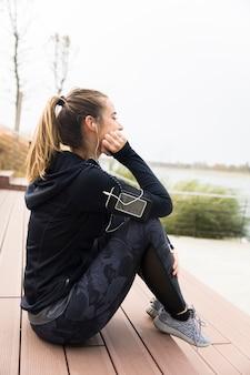Frustriertes und müdes sportliches frauensitzen im freien auf treppe