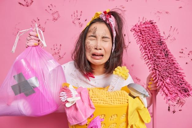 Frustriertes unzufriedenes hausmädchen weint unglücklich, dass es müde ist, das haus zu putzen, hält müllsack und mopp sammelt alle schmutzige wäsche einzeln auf rosa