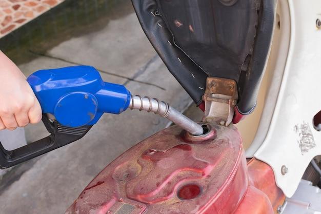 Fügen sie benzinkraftstoff zum motorrad an einer benzinstation mit einer hand hinzu