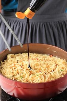 Fügen sie süße sojasauce in die pfanne mit nudeln hinzu, kochprozess, der asiatisches köstliches essen herstellt, bakmi goreng