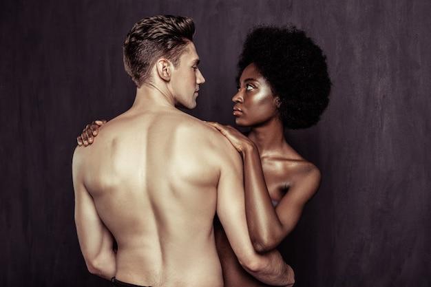 Fühle den funken. schönes junges paar, das einander ansieht, während es einen funken zwischen ihnen fühlt