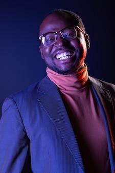 Fühle erfolg. freudiger dunkelhäutiger mann, der eine brille trägt, während er über sein geschäft nachdenkt