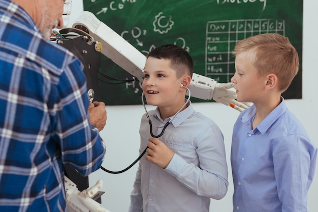 Fühle es. netter angenehmer junge, der ein stethoskop trägt, während er auf den elektronischen mechanismus hört