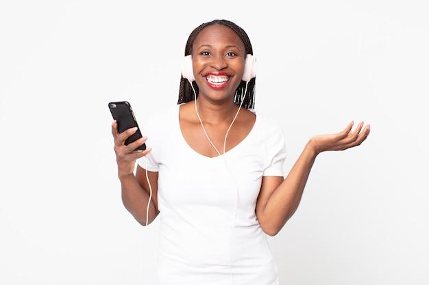 Fühlen sie sich glücklich, überrascht, eine lösung oder idee mit kopfhörern und einem smartphone zu verwirklichen