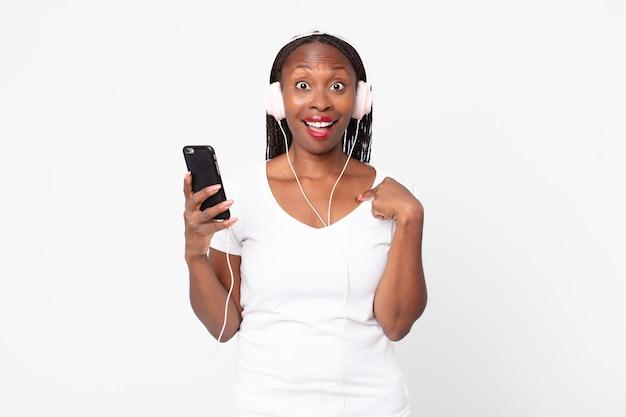 Fühlen sie sich glücklich und zeigen sie auf sich selbst mit einer aufregung mit kopfhörern und einem smartphone