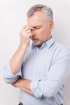 Fühlen sie sich müde und gestresst. frustrierter älterer mann im hemd, der den kopf mit den fingern berührt und die augen geschlossen hält, während er vor weißem hintergrund steht