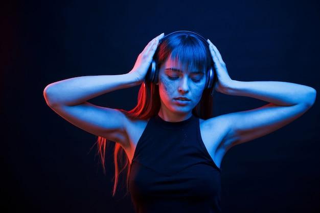 Fühlt sich gut an. studioaufnahme im dunklen studio mit neonlicht. porträt des jungen mädchens