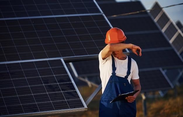 Fühlt sich müde. männlicher arbeiter in blauer uniform im freien mit solarbatterien am sonnigen tag.