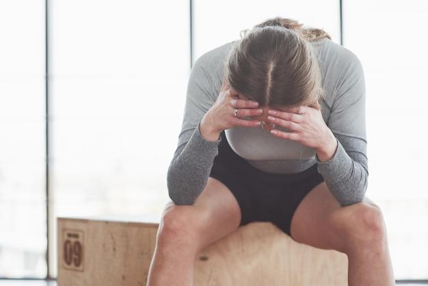 Fühlt sich müde. sportliche junge frau haben fitness-tag im fitnessstudio zur morgenzeit