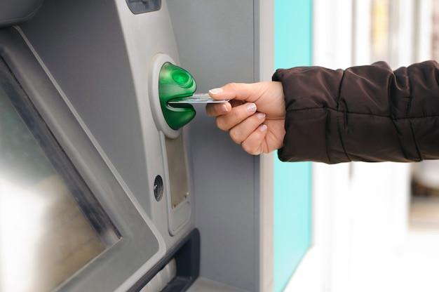 Führen sie die geldautomatenkarte von hand in den bankautomaten ein, um geld abzuheben
