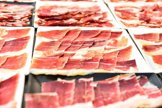 Führen sie einige teller geschnittenen serrano-schinkens während einer veranstaltung einzeln auf.