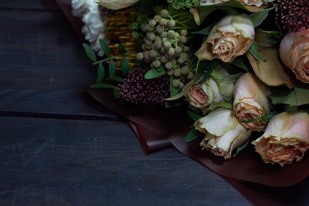Führen sie nahaufnahmeblumenstrauß in den pastellfarben in der weinleseart auf dunkelheit einzeln auf