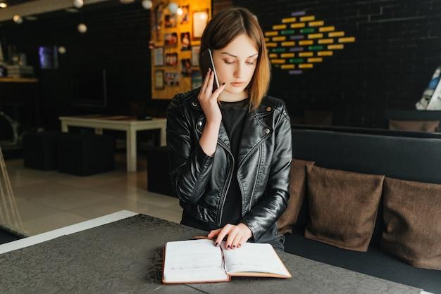 Führendes geschäftsgespräch der jungen geschäftsfrau am telefon und am lesen