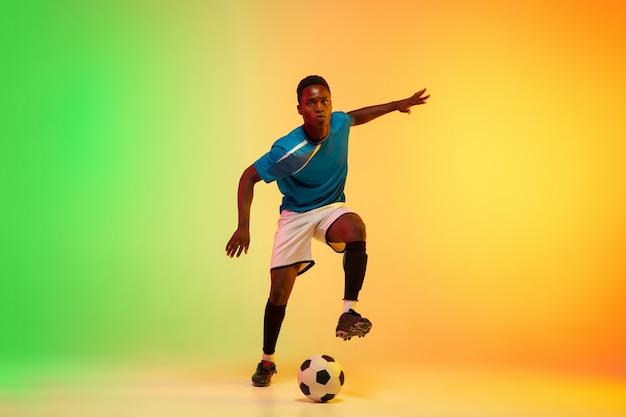 Führer. afroamerikanischer männlicher fußball, fußballspielertraining in aktion einzeln auf gradientenstudiohintergrund im neonlicht. konzept der bewegung, aktion, erfolge, gesunder lebensstil. jugendkultur.