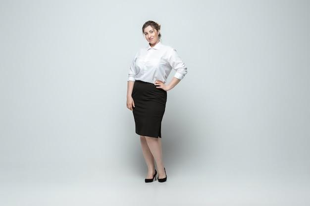 Führer. junge frau in bürokleidung. körperpositiver weiblicher charakter, feminismus, sich selbst liebend, schönheitskonzept. plus-size-geschäftsfrau auf grauer wand. chef, schön. inklusion, vielfalt.
