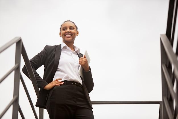 Führer, lächelnd. afroamerikanische geschäftsfrau in bürokleidung lächelnd, sieht selbstbewusst und glücklich aus, beschäftigt. konzept für finanzen, wirtschaft, gleichstellung und menschenrechte. schönes junges modell, erfolgreich.