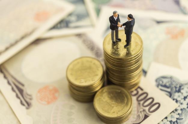 Führergeschäftsmann entspricht händedruckstand unter auf stapel münze und geld.