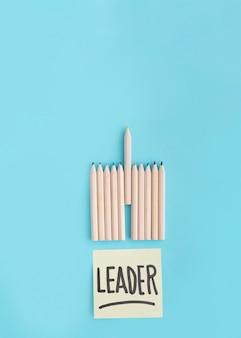 Führertext auf klebender anmerkung mit reihe des farbigen bleistifts auf blauem hintergrund
