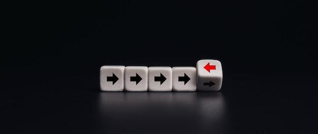Führung, einzigartig, konzept anders denken. weiße würfelblöcke, die mit rotem pfeil in die entgegengesetzte richtung zeigen, schwarze pfeile auf dunklem bannerhintergrund, minimaler stil.