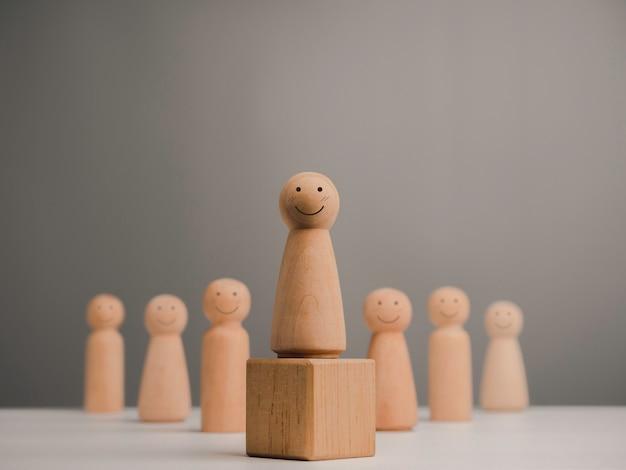 Führungsfrau, influencerin, frauen im führungspositionskonzept. holzfigur, glückliche und starke frau mit lächelndem stehen auf der box und team, minimalistischer stil.
