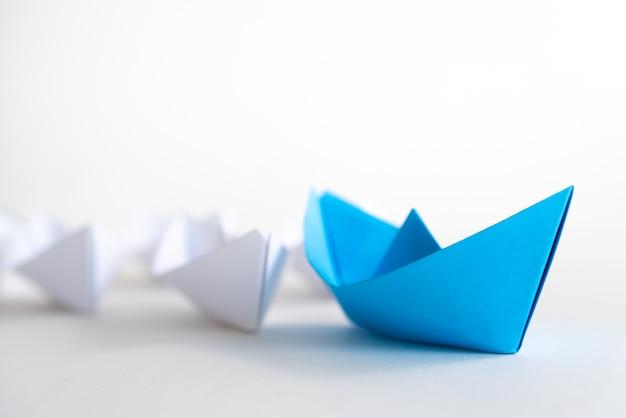 Führungskonzept. blaues papierschiff führen unter weiß. ein führerschiff führt andere schiffe.