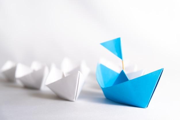 Führungskonzept. blaues papierschiff mit markierungsfahne führen unter weiß.