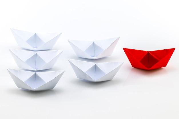 Führungskonzept mit rotem papierschiff, das unter weiß führt.
