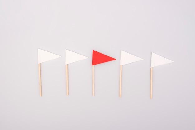Führungskonzept mit roter papierfahne, die unter weiß führt. anderes konzept.