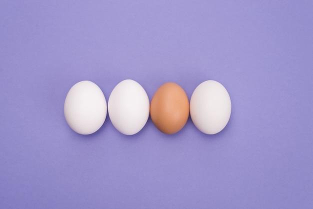 Führungskonzept. oben oben nahaufnahme ansicht foto von drei gleichen eiern und einem ei mit brauner schale über violettem farbhintergrund isoliert