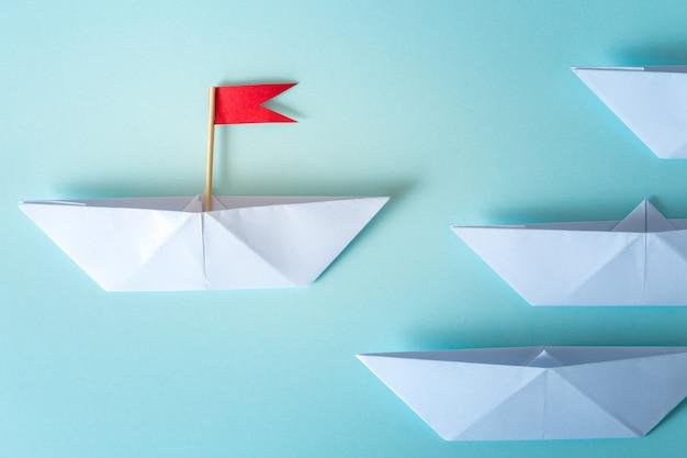 Führungskonzept unter verwendung der papierlieferung mit roter fahne auf blauem hintergrund