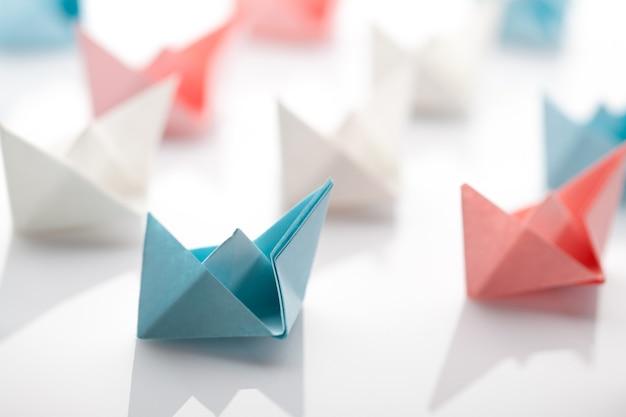 Führungskonzept unter verwendung von papierschiff unter weiß