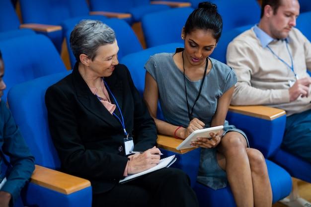 Führungskräfte, die an einem geschäftstreffen mit einem digitalen tablet teilnehmen