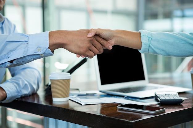 Führungskräfte, die sich während des meetings die hand geben