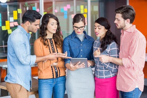 Führungskräfte diskutieren über digitales tablet