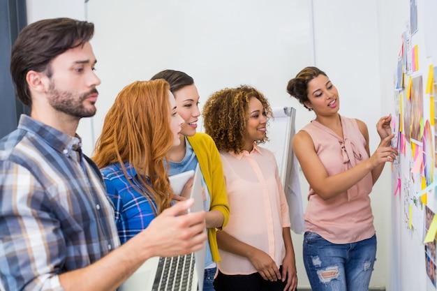 Führungskräfte diskutieren während des meetings über haftnotizen