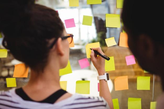 Führungskräfte in unternehmen auf haftnotizen schreiben