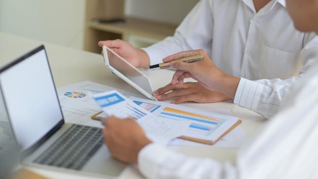 Führungskräfte mit tablet bewerten die situation des unternehmens