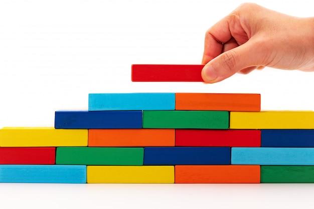 Füllen sie das geschäftslösungskonzept aus, ein stück holzblockpuzzle, das auf holzstapel gesetzt wird