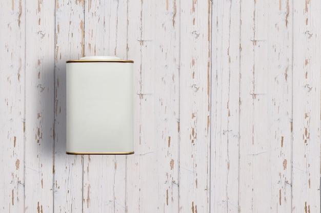 Füllen sie die weißen teedosen der ansicht auf, die auf weißem hölzernem hintergrund lokalisiert werden. passend für ihr designprojekt.