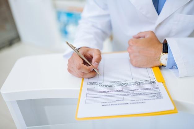 Füllen sie informationen aus. stilvoller apotheker mit uhren, faust auf tisch gelehnt