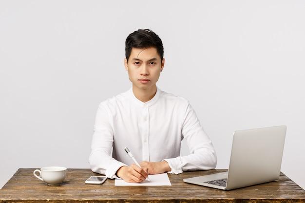 Füllende dokumente des netten lächelnden asiatischen jungen unternehmers im büro