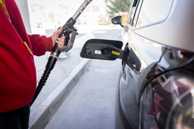 Füllendes benzin der frau in einem auto