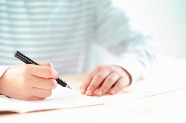 Füllfederhalter, der vom mann mit kleinem notizbuch auf schreibtisch hält