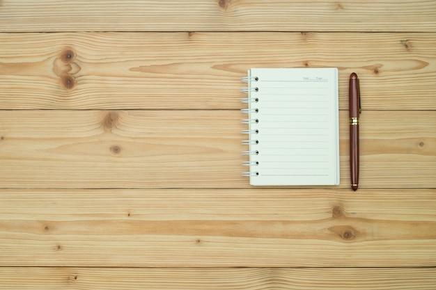 Füllfederhalter oder kugelschreiber mit notizbuchpapier auf holztisch